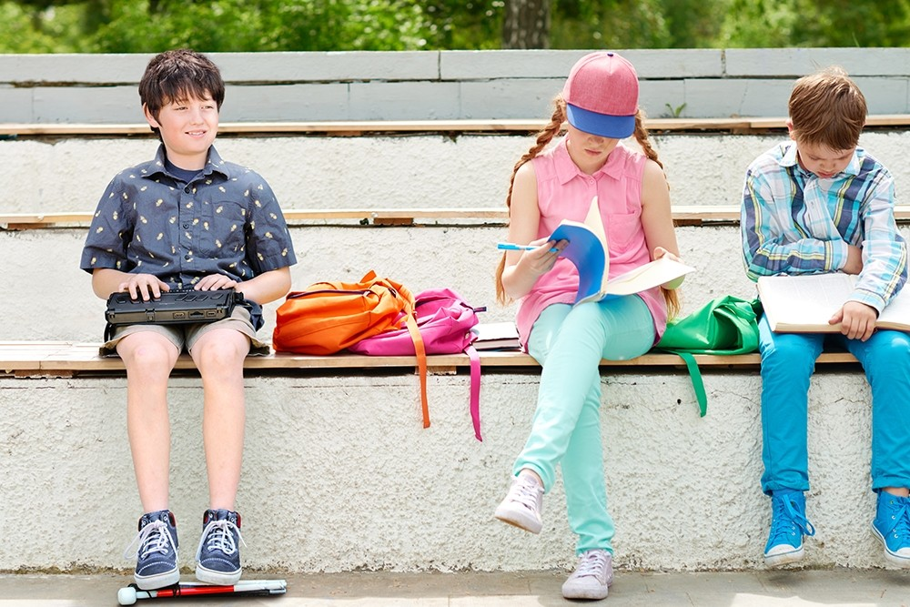 Students sitting outside on the bench with one boy using Braille Note Plus Plus