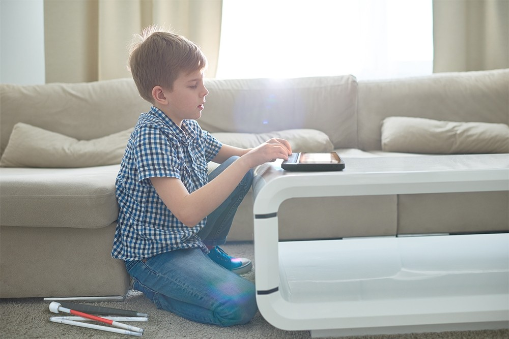 A boy using a BrailleNote Plus in living room