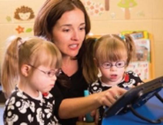 Two girls with teacher using iPad