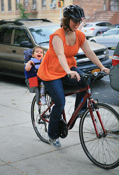 Emmett riding in a modified seat on a bike with his mother.